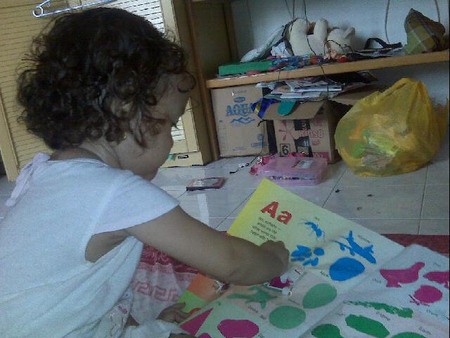 Anakku sedang bermain dengan gambar-gambar. Salah satu kegiatan anak yang positif.